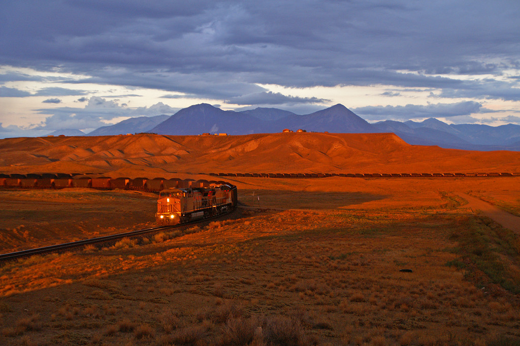 The last rays of sunlight cast a long shadow on a loaded UP coal train near Rogers Mesa, CO