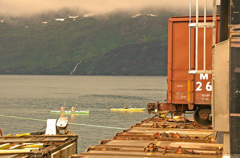 The Alaska Rail Marine Barge is in the process of being unloaded in Whittier, AK as several kayakers paddle by in Prince William Sound.