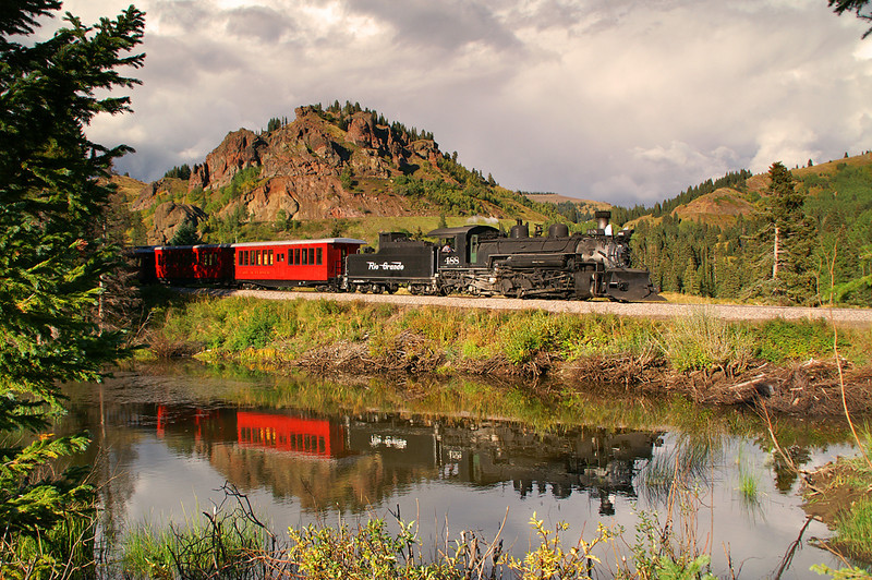 Rio Grande 488 is reflected in Perry's Pond while in the background can be seen the summit of Cumbres Pass.