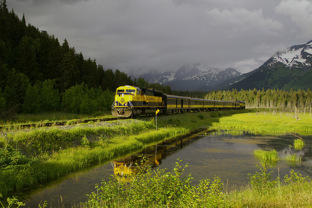 A northbound cruise train has a momentary burst of sunshine following a rain squall. This shot is near Girdwood, AK