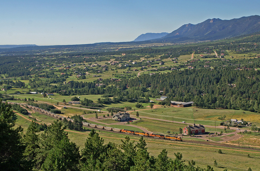 An empty BNSF coal train is headed north through Palmer Lake, CO as seen from the surrounding bluffs on a beautiful Colorado day.