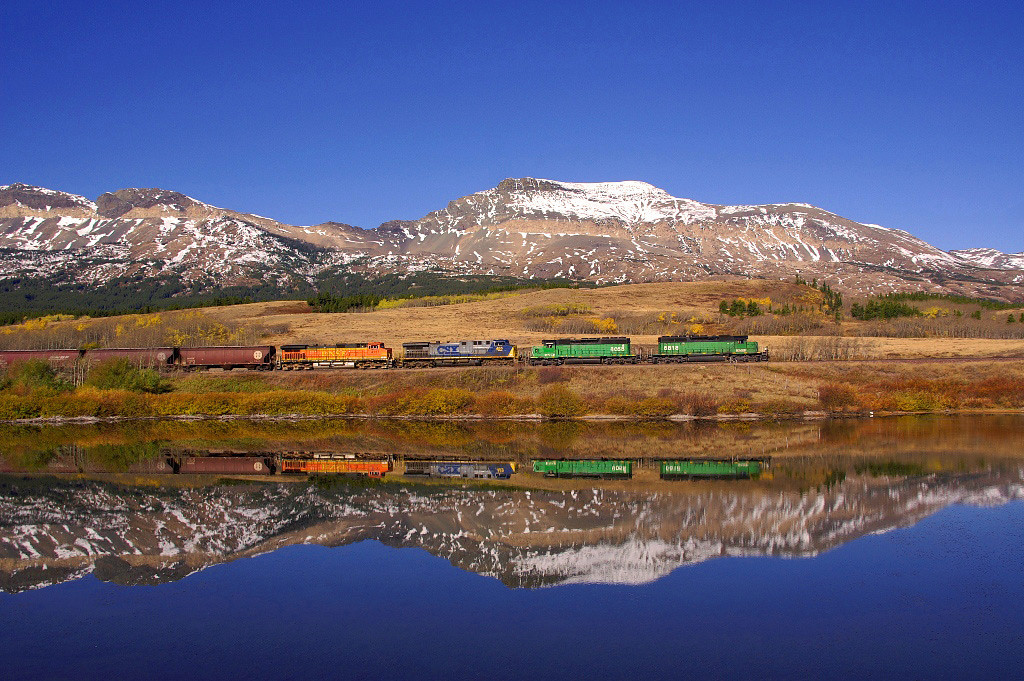 In northern Montana a train rolls along BNSF's Highline. Seen here reflected in a pond that for the prior week I was here was continually wind blown so when I saw this pond as smooth as glass I felt fortunate.