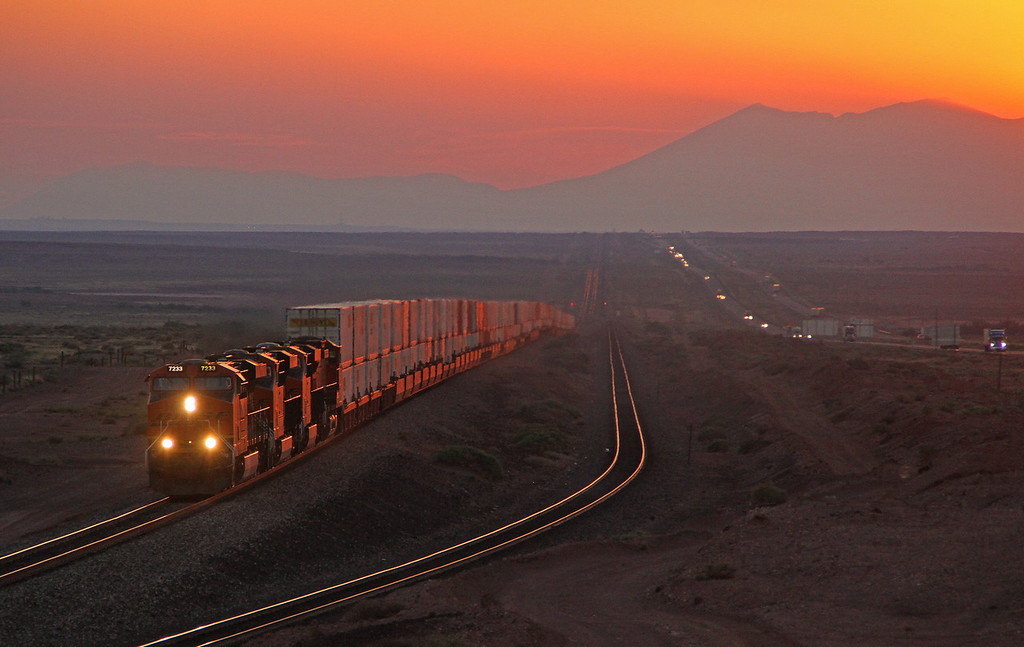 11-23-12: At the end of a beautiful day a matching sunset. A BNSF train is about to arrive at Winslow, AZ for a crew change while traffic on parallel Interstate 40 rolls by.