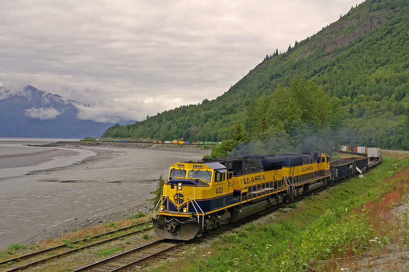 An intermodal train rolls along Turnagain Arm in the small town of Indian enroute to the barge at Whittier.