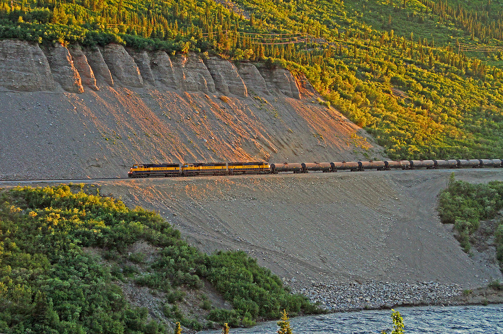 Summer time in Alaska allows this shot of a southbound freight train in the waning light at 12:06 AM. The train is along the Nenana River and is about to enter Denali Park home of the highest mountain in North America, Mt. Denali.