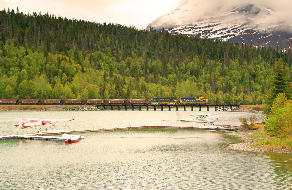 An Alaska Railroad ballast train crosses the wood trestle over Upper Trail Lake at Moose Pass, Alaska.