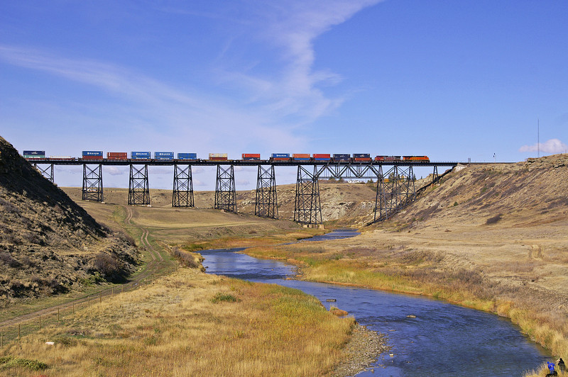 A BNSF eastbound double stack train crosses a small river at Cutbank, MT on a very nice fall day.