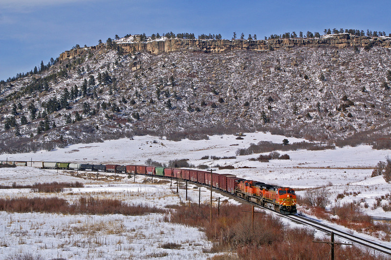 A recent snow fall adds to the scene as a freight works its way south towards Colorado Springs, CO