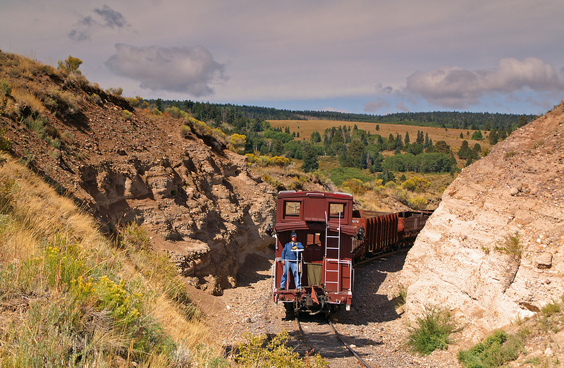 The conductor rides the caboose through the high country of Colorado.