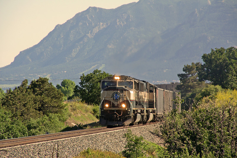 A BNSF train rolls north returning to the coal fields of Wyoming. In the background is Cheyenne Mountain. Home of Norad.