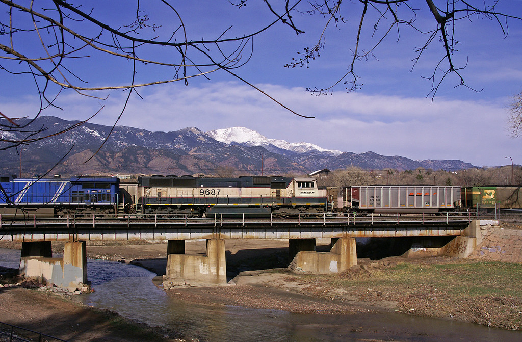 Empty and loaded coal trains cross Monument Creek as Pikes Peak stands watch on a sunny Colorado Springs, CO morning.