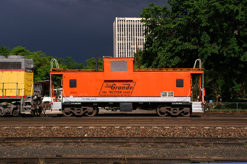 Rio Grande caboose baskes in the sunshine as a storm brews to the east.