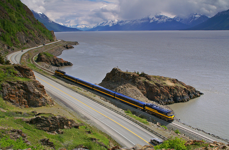 An Alaska Railroad cruise train is headed for Seward along Turnagain Arm. Highway 1 to the left of the train will also end in Seward.