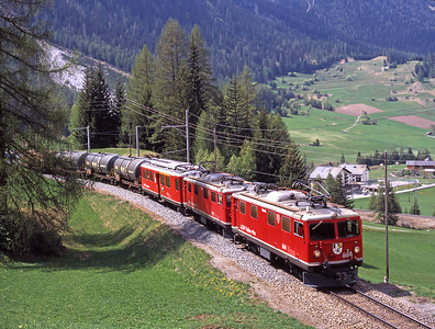 A pair of 1947 built Ge 4/4 I veterans 604+603 haul a freight up the middle level above Bergün 1/5/07.  The first vehicle is Bernina motorcoach no. 41.