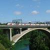 A train of IC2000 double-deck stock crossing the four-track concrete bridge over the Aare at Bern.