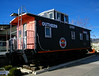 Cupola caboose on display between model train hobby store and renovated depot/museum.