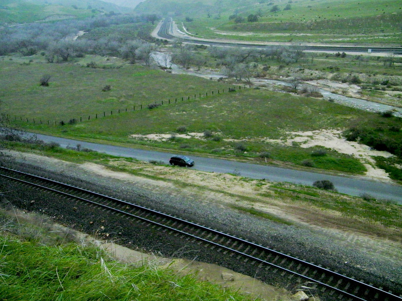 Another location change afforded this overview.  The rails at top lead downhill to Bakersfield, while the tracks in foreground head to Tehachapi (Pass and town) and beyond.  And on the road a center is the MayhemMobile, Executive Director Alice at the wheel, on the way to retrieving Executive Director WhoozOn1st.  The watercourse between the road and upper rails is Tehachapi creek.