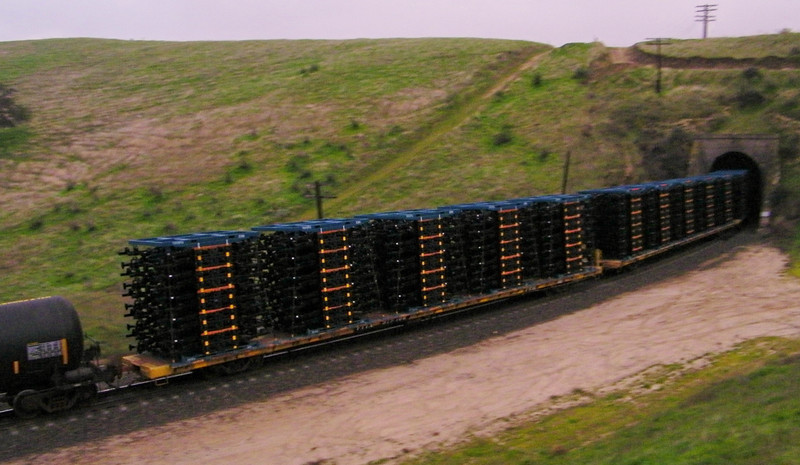 The flatcars heading into the tunnel were burdened with what appeared to be vehicle frames; can't see with the bad focus, but the blue jig things on top and bottom of the stacks say Toyota on 'em.