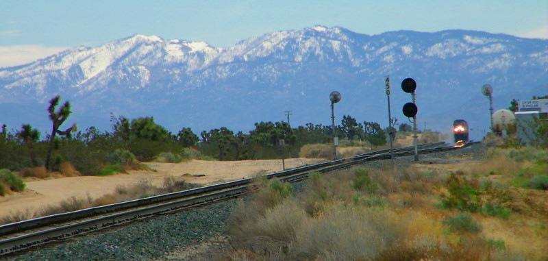 With snowcapped southern California mountains as backdrop, the Pacific Railroad Society's Diamond Jubilee Special passes Phelan siding outside Hesperia, approaching a grade crossing at speed.
