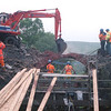 The pneumatic drills proving to be futile the digger is brought into finish off the remaining part of the arch of bridge of 87, 18/7/1998