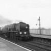 An unidentified West Country at the head of fast moving westbound milk empties at Templecombe on 25/04/64.