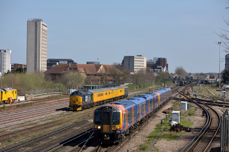 With duties apparently over for the day 37688 and test train 1Q40 are stabled in Woking Yard as Desiro 450543 scuttles past with the 11.12 from Waterloo to Basingstoke<br /> <br /> 7 April 2015