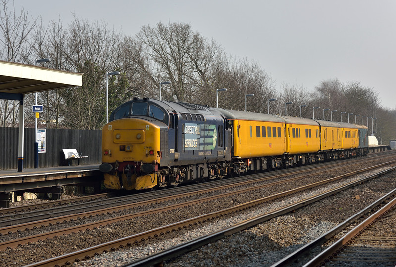37688 is on the rear of  test train 1Q82 behind coaches  9481 6261 999550 1256 with 73201 doing the work up front.<br /> Seen as it raced through Hersham bound for Waterloo.<br /> <br /> 8 April 2015