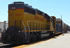 The UP locomotive is shoving a string of autoracks and that flatcar to the Ventura County Railway route to Port Hueneme, the only deepwater harbor between Los Angeles and San Francisco.