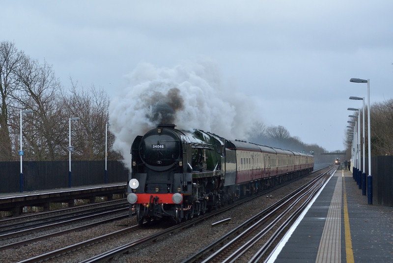 Rebuilt West Country No 34046 Braunton echoes the joy of steam on the SWML as it races through Hersham with 1Z92 The Salisbury Christmas Diner from Waterloo.<br /> <br /> 23 December 2013