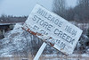 Fresh snow on old mileage sign in Moosonee. Mileage 186.04 Store Creek elevation 18.00.
