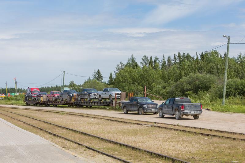 Vehicles going south on Polar Bear Express. Flatcars ONT 100500, 100501, 100504.