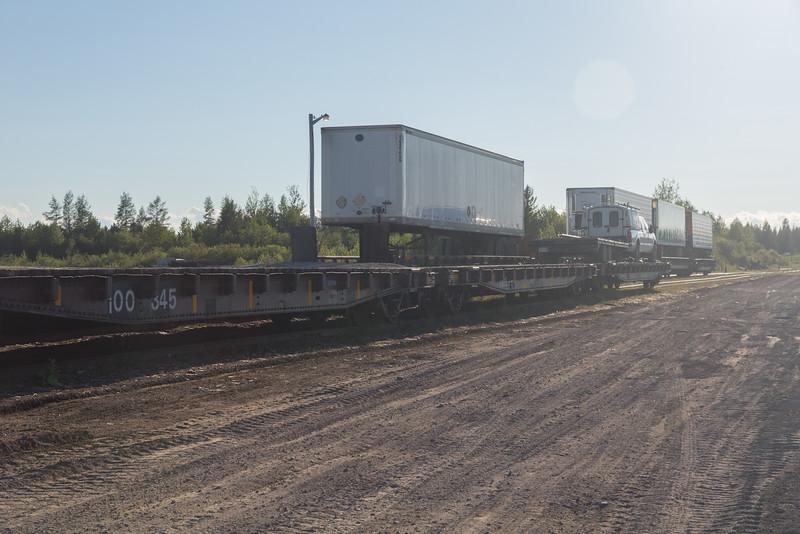 Trailers on flatcars along Airport Road in Moosonee.