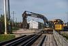 Excavator with metal shears crossing tracks.