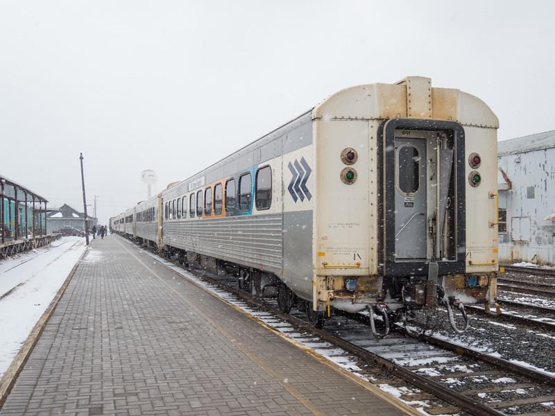 Polar Bear Express coaches along station platform in Moosonee. Light blowing snow.