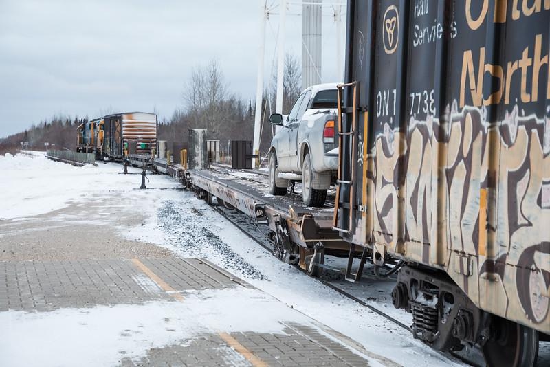 Polar Bear Express looking forward from boxcar behind flatcars towards locomotives on bridge.