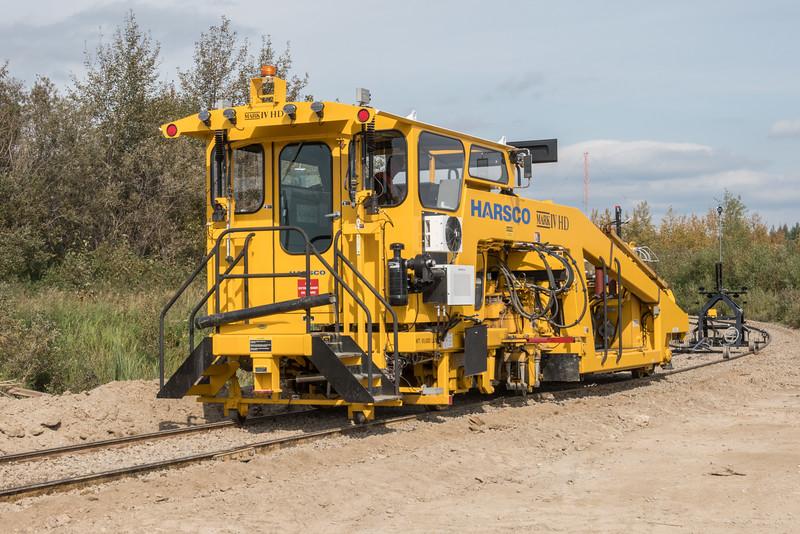 Harsco Mark IV HD tamper with projector buggy working on tracks crossing Ferguson Road in Moosonee.