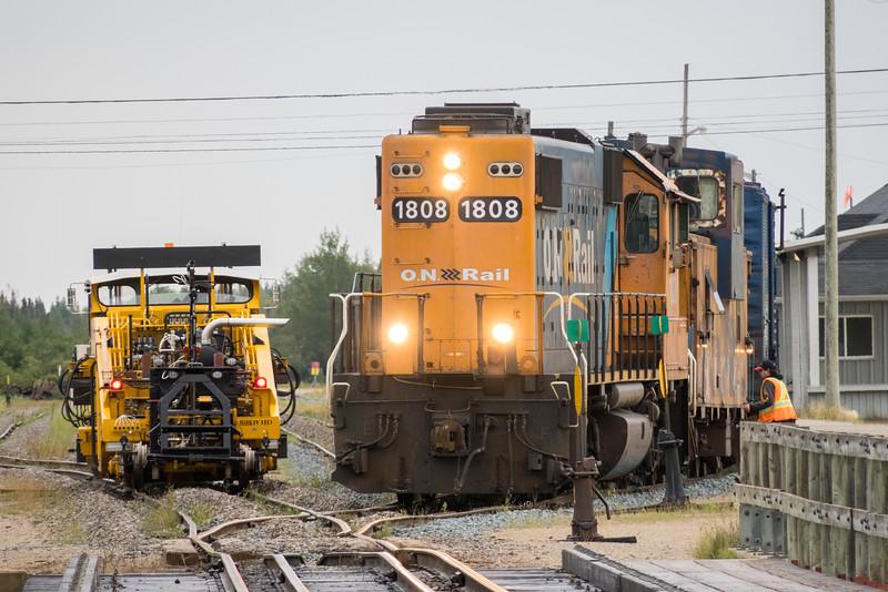 Tamper waiting for rock train behind GP38-2 1808 to depart.