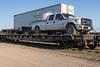 Ontario Northland Railway flatcar 100329 with Trilinks pickup truck and trailer along Airport Road in Moosonee.