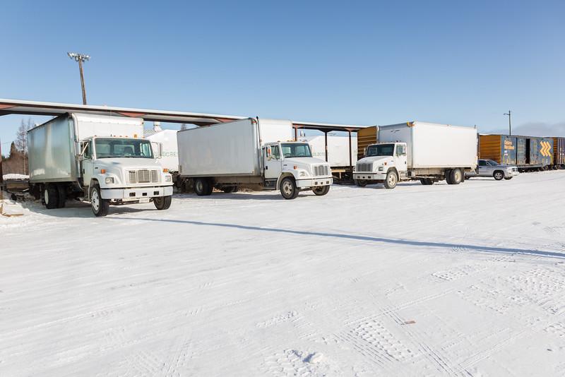 Three white trucks at Moosonee station.