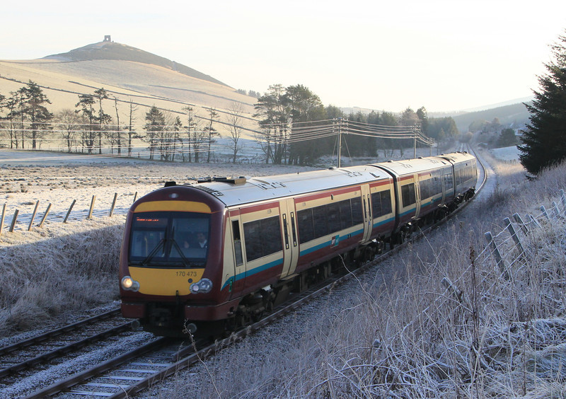 SPT liveried 170473 passes ruins of Dunideer Castle between Insch and Kennethmont on 15th January 2012