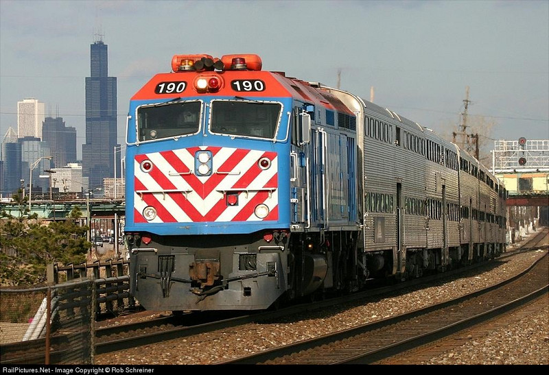 Metra heads out of the city as it arrives in Cicero, IL with the Chicago skyline in the background.