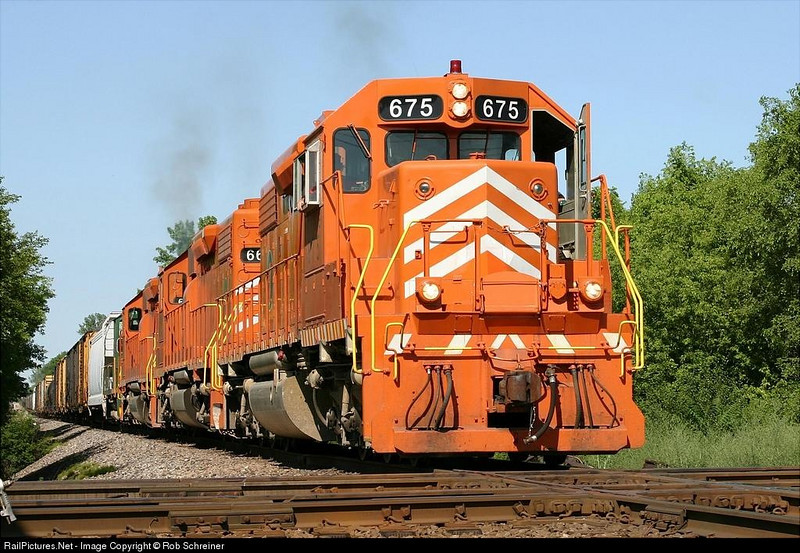 EJ&E runs the Western subdivision road train back to Joliet from Rondout. Three SD38's lead an offline switcher over the diamonds in Barrington, IL.