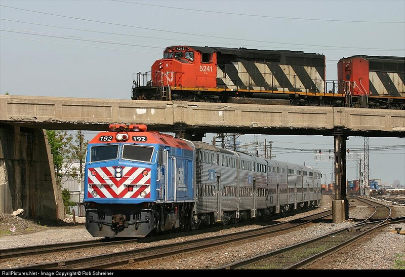 A Metra BNSF west line commuter train flys under a Canadian National freight train in Berwyn, IL