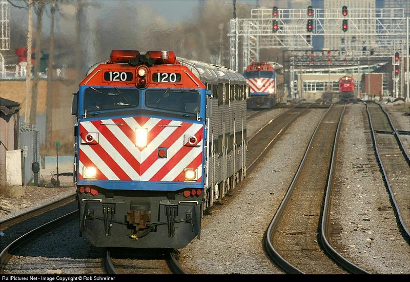 The CP Rail Elgin subdivision is busy as the Metra rush takes place. These two commuter trains head towards Elgin, rounding the curve at Hanson Park in Chicago.