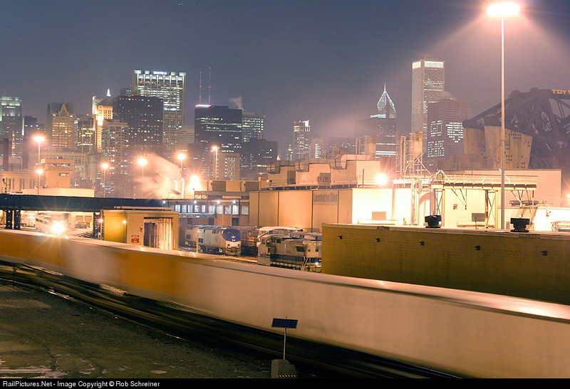 A UP intermodal train snakes thru Canal St. on a very cold Chicago night. Don't miss the window display in the skyline.