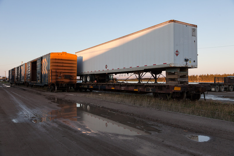 Boxcars and trailer on flatcar on Ontario Northland Railway track along the Moose River (barge docks) in Moosonee, Ontario.