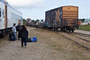 Locomotives and head end section of Polar Bear Express pull away from passenger cars to drop off a box car on freight track and flat cars carrying vehicles at unloading platform.