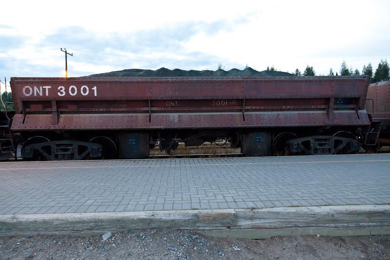 Side view of air dump ballast car 3001 at Moosonee station platform.