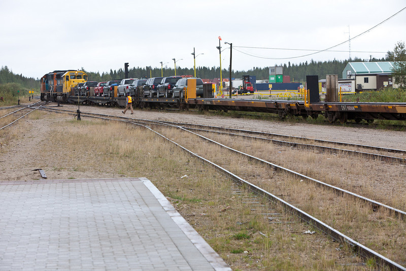 Locomotives and flatcars for motor vehicles at the head of the Polar Bear pull ahead of the passenger cars, then back up to pick up empty flatcars to be used on the return journey. These are put aside while the newly arrived flatcars are brought into the loading platform so passengers and local residents can retrieve their vehicles.