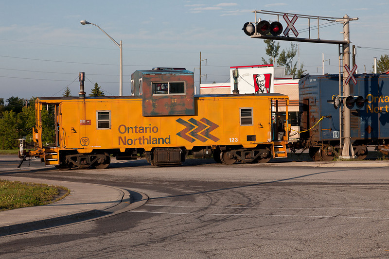 Caboose 123 crossing highway in Cochrane, in consist of gravel train.
